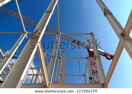 Construction of a new office building with a high construction crane on a background sky