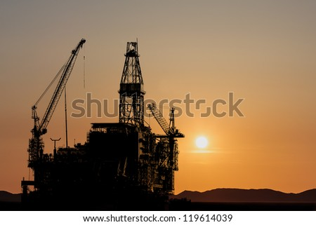 Construction of a new oil platform during sunset