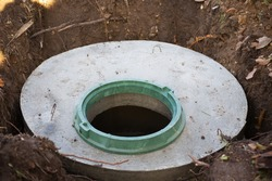 Construction of a septic tank. Large concrete rings embedded in the ground, from above an open sewer hatch, unprotected by a cover from falling.