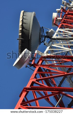 Construction of a telecommunications tower with antennas against a blue sky