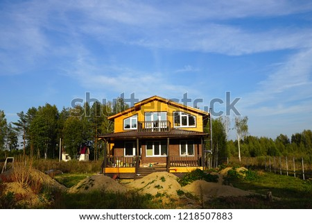 Construction of a wooden house. Rustic new building, cottage with balcony, veranda, porch. house near a tree #1218507883