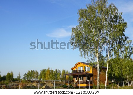 Construction of a wooden house. Rustic new building, cottage with balcony, veranda, porch. With high birch in the foreground, a house near a tree #1218509239