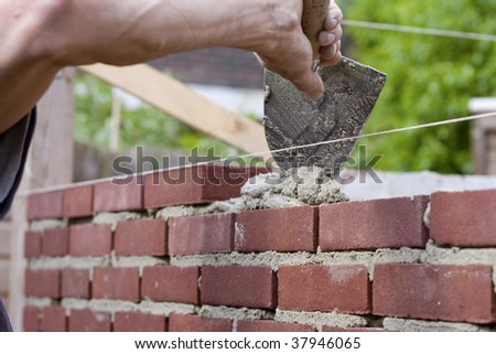 Construction of brick wall. Trowel spreading cement on bricks