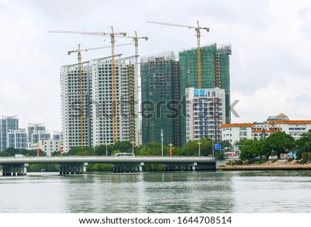 Construction of buildings in a new residential area of the city with tower cranes. Industrial and tourist development of Sanya, Hainan island, China