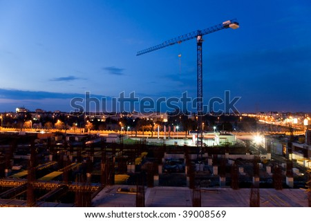 construction of buildings with crane at sunset