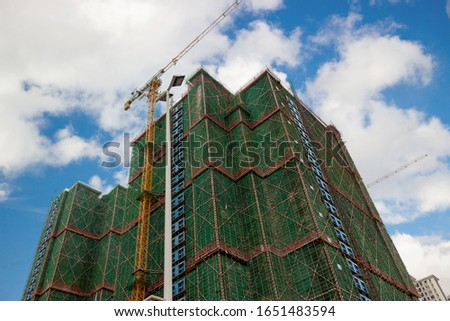 Construction of buildings with tower cranes against blue sky background. New construction site in modern city. Business and tourist development of Sanya, Hainan island, China.