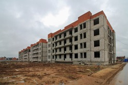 Construction of low-rise monolithic brick block of houses according to standard design. Empty construction site - project is not built, . Unfinished construction. Four storey country house in suburbs.