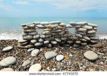 construction of many pebbles on a sea coast near water.