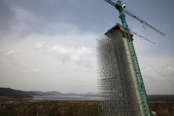 Construction of modern high-rise ski-jump in Shchuchinsk city, Kazakhstan. Concrete tower with cranes and scaffoldings. mountains, lake and blue sky with clouds on background.
