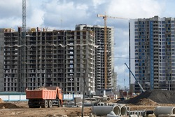 Construction of modern multi-storey buildings. New development of a residential area. House frames, construction cranes and building materials at the construction site.