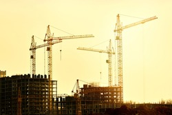 Construction of new residential high-rise buildings. Against the background of a yellow sunset sky.