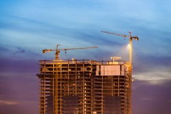 Construction of office building on purple sunset with two tower cranes