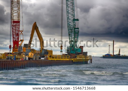 Construction of offshore section of gas pipeline on bottom of Baltic sea Nord stream-2. Pier goes into Narva Bay, excavator aligns bottom under bed of gas pipeline. Auxiliary vessels at sea Photo stock ©