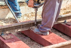 construction of railway track with wooden sleepers. Worker with a drill makes the hole in which the bolt that holds the rail fixed on the sleeper will be fixed.