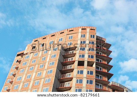 construction of the brick building over the blue sky background