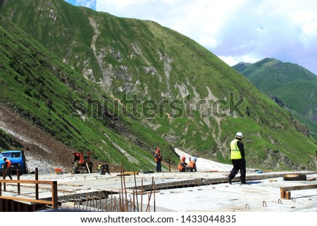 Construction of the bridge in the mountains. Concrete slabs with metalware and several workers and their foreman standing. #1433044835