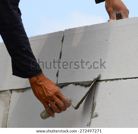 Construction of the wall of white brick.