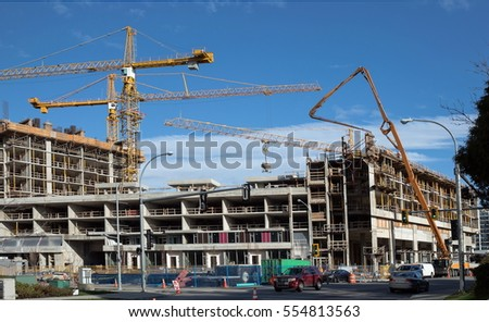 Construction of  three new high-rise building,  cranes, machine for pouring cement. - Shutterstock ID 554813563