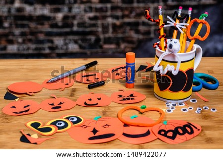 Construction paper jack-o-lanterns,  being made.  Many crafts like cat faces, pumpkins, pipe cleaners, construction paper and tools for crafting and scrapbooking.  Room for Copywriting