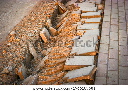Construction piles of sand, stones lying on the sidewalk near the pits for installing between the roadway and the footpath. Broken asphalt and pavement. Repair of road works. Stock photo ©