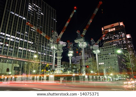 construction place in center of Tokyo among huge skyscrapers by night