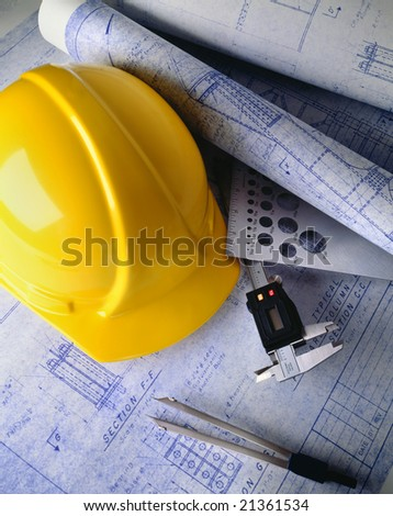 Construction plans with hard hat and drawing tools