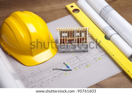 Construction plans with helmet and drawing tools on blueprints