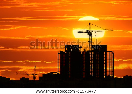 Construction project silhouette against sunset sky with big sun setting down