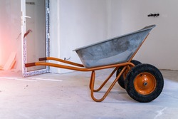 Construction pushcart or wheelbarrow in building hallway with natural light. Closeup.