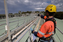 Construction rope access engineer planer wearing safety helmet harness, holding permit order drawing paper work and pointing where roof work repairing located  to be completed