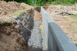 Construction shaft by a concrete wall as a border between two properties outside in backyard.