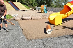 Construction side work. making a floor with the rubber beads on playground, New childrens playground under construction in Arendal, Norway. Slide in the park children's playground. big plastic toy,