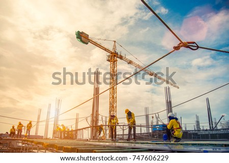 construction site and sunset , structural steel beam build large residential buildings at construction site .