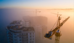 Construction site at dawn. Tower cranes over fog on the background of the morning sun. Drone view