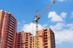 Construction site background. High-rise red brick building under construction. Crane near the building under construction.
