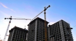 Construction site background. Hoisting cranes and new multi-storey  buildings. Industrial background.