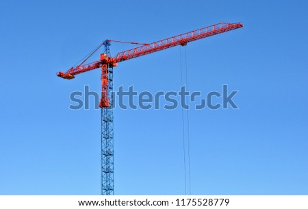 Construction site. Big industrial tower crane with blue sky in background. Contemporary urban landscape. Modern civil engineering. Beautiful photo of a construction crane against sky