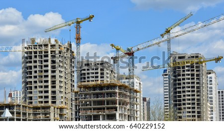 Construction site. Big industrial tower cranes with unfinished high raised buildings and blue sky in background. Scaffold. Modern civil engineering. Contemporary urban landscape.