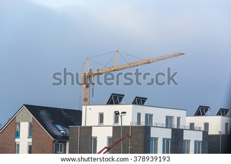 Construction site, construction area with row houses and a crane.