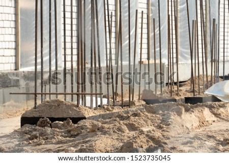 Construction site. Construction of a new building. Unfinished building with reinforced structures with metal mesh. Mud, lots of sand.