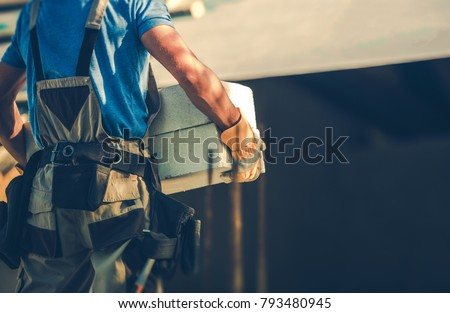 Construction Site Contractor Moving Heavy Building Materials in His Hands. Residential Development Industry. #793480945