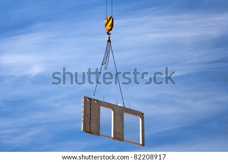 Construction site crane is lifting a precast concrete wall panel in the sky