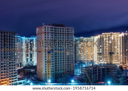 Construction site, cranes and multi-storey unfinished houses at night in winter. Сток-фото ©