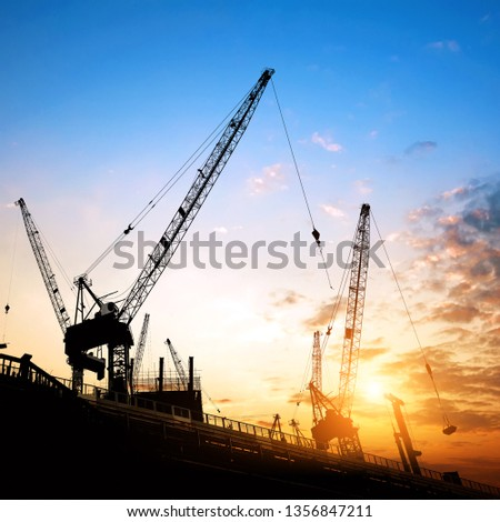 Construction site, cranes and scaffolding silhouette.