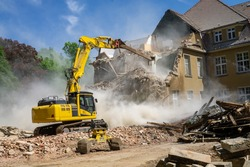 Construction site digger yellow demolishing house for reconstruction