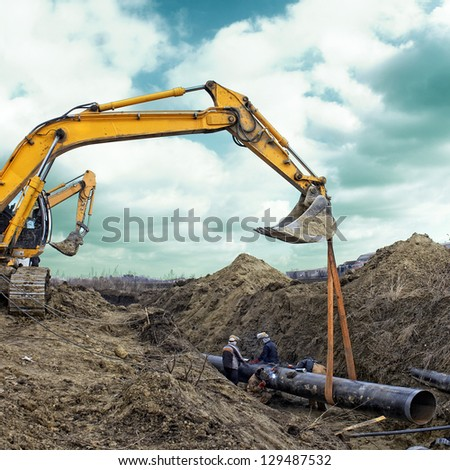 Construction site excavator wearing metal pipe
