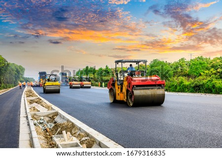 Construction site is laying new asphalt road pavement,road construction workers and road construction machinery scene.highway construction site landscape.
