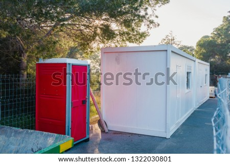 Construction Site Living Container. Outdoor portable red toilet. WC on the construction site.