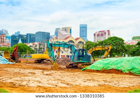 Construction site machinery and digging excavators working on Singapore downtown street