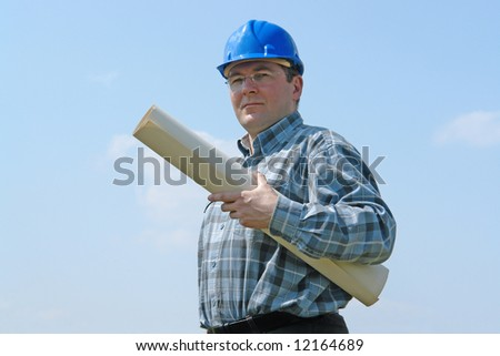 Construction site manager wearing blue helmet holding roll of building plans over blue sky